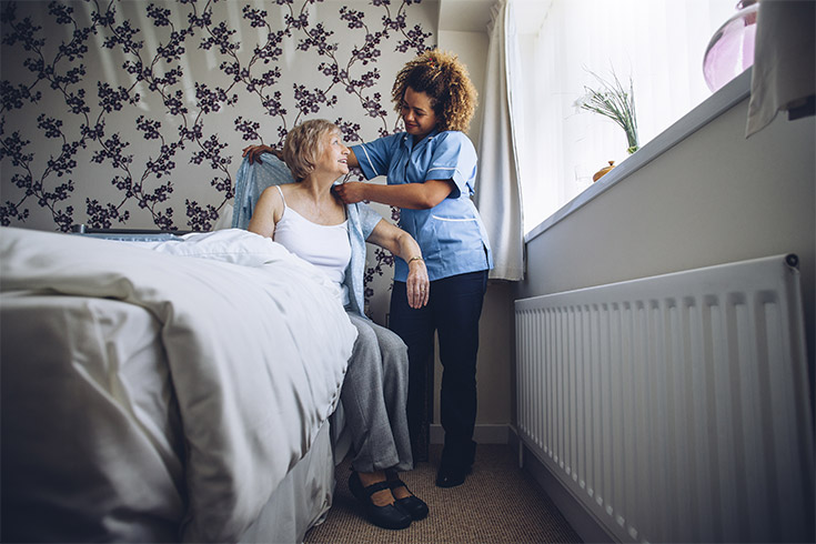 Female care worker helping patient out of bed